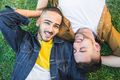 Gay couple laying down on the grass at the park. - PhotoDune Item for Sale