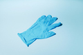 Protective medical glove on blue background. Top view. Copy space. Minimal medical concept. Medical - PhotoDune Item for Sale