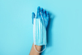 Hand with blue medical gloves holding medical facemask on blue background. Banner with copy space - PhotoDune Item for Sale
