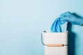 Hand in medical gloves throws medical mask into trash can on blue background. Quarantine over. Covid - PhotoDune Item for Sale