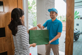 delivery smiling to woman while holding shopping bag - PhotoDune Item for Sale