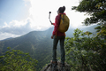 Woman hiker taking pictures with action camera in spring mountain - PhotoDune Item for Sale