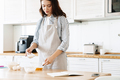 Image of focused young woman preparing dough while cooking pie - PhotoDune Item for Sale
