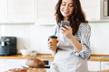 Image of happy baker woman using cellphone while drinking coffee - PhotoDune Item for Sale