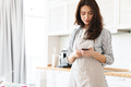 Image of focused brunette woman using cellphone while cooking pie - PhotoDune Item for Sale