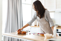 Image of focused brunette woman wearing apron cooking pie with recipe - PhotoDune Item for Sale