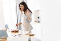 Image of smiling brunette woman waving hand while cooking muffins - PhotoDune Item for Sale