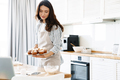Image of pleased brunette woman smiling and holding muffins - PhotoDune Item for Sale
