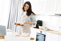 Image of pleased woman apron smiling and pointing hand at muffins - PhotoDune Item for Sale