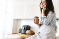 Image of happy baker woman talking on cellphone while drinking coffee - PhotoDune Item for Sale