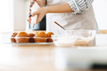 Cropped image of young caucasian woman cooking muffins with cream - PhotoDune Item for Sale
