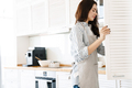 Image of focused young woman opening cupboard while cooking pie - PhotoDune Item for Sale