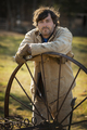 A man in overalls wearing work gloves,leaning on a round metal wheel with spokes on a farm - PhotoDune Item for Sale