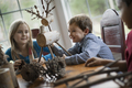 Three children sitting at a table in family home. A twig reindeer in the centre - PhotoDune Item for Sale