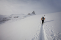 Two skiers ascending a ridge in mist and cloud conditions in snow in the mountains - PhotoDune Item for Sale
