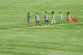 A group of children walking up a sloping path in height order following each other - PhotoDune Item for Sale