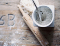 A rolling pin and jar of flour on a worn tabletop,View from above - PhotoDune Item for Sale