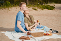 Picnic on beach with food and drinks. Young boy and girl sunbathing - PhotoDune Item for Sale