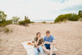 Picnic on beach with food and drinks. Young boy and girl sitting on sand - PhotoDune Item for Sale