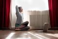 Woman in sitting yoga pose cow face asana during online lesson on laptop. - PhotoDune Item for Sale