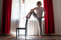 Young woman doing yoga doing lone raised leg balance using chair. - PhotoDune Item for Sale