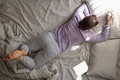 Young woman send message, chatting with her friends resting at home on bed. - PhotoDune Item for Sale