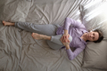 woman lying on bed in the morning and doing stretching exercise from yoga - PhotoDune Item for Sale