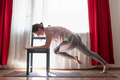 Woman doing push ups exercises for training chest and arms muscles at home - PhotoDune Item for Sale