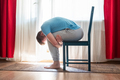 mature man doing childs pose in yoga using chair - PhotoDune Item for Sale
