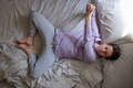 woman doing supta baddha konasana on bed in the morning warming up - PhotoDune Item for Sale