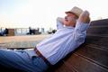 Senior hispanic man in summer hat sitting outdoors on bench. - PhotoDune Item for Sale