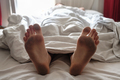 Dirty bare feet of a sleeping person showing out of the blanket - PhotoDune Item for Sale