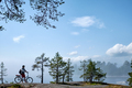 young men riding a bicycle on bike trail at the lake in the morning. - PhotoDune Item for Sale