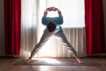 man working out standing in asana Wide Legged Forward Bend - PhotoDune Item for Sale