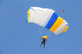 Skydiver under canopy of yellow with blue parachute in cloudless sky - PhotoDune Item for Sale