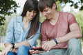 Young couple smiling as they read a phone message - PhotoDune Item for Sale