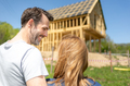 Couple looking at their new house under construction, planning future and dreaming - PhotoDune Item for Sale