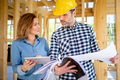 Female homeowner consults blueprints with architect or engineer - PhotoDune Item for Sale