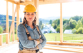 Proud female worker posing on building site with frame house construction in background - PhotoDune Item for Sale