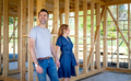 Wife and husband visiting building site of their new house with construction in background - PhotoDune Item for Sale