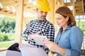 Female homeowner consults blueprints with architect or engineer on construction site - PhotoDune Item for Sale