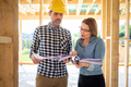 Homeowner consults blueprints with architect or engineer on construction site - PhotoDune Item for Sale
