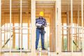 Builder reading blueprints plan of wood construction frame house - PhotoDune Item for Sale