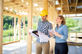 Architect or engineer with blueprints meeting with owner of building house on construction site - PhotoDune Item for Sale