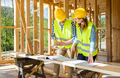 Engineers working on construction site holding blueprints of wood frame house - PhotoDune Item for Sale