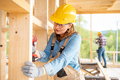 Female worker at construction site during work with wood frame house - PhotoDune Item for Sale