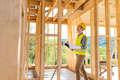 Engineer with hardhat and blueprints on building site of wood frame house under construction - PhotoDune Item for Sale