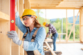 Woman worker at building site of wood frame house using level tools - PhotoDune Item for Sale