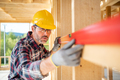 Worker using level tool measure frame house construction - PhotoDune Item for Sale