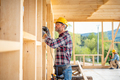 Worker using drill working on construction of wood frame house - PhotoDune Item for Sale